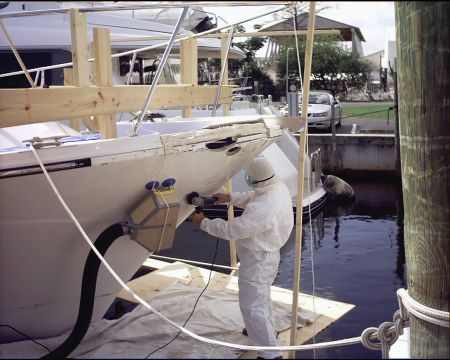 An image of a Dennis Boatworks employee working on the exterior of a yacht.
