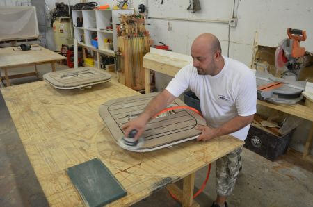 An image of a Dennis Boatworks employee sanding wood.