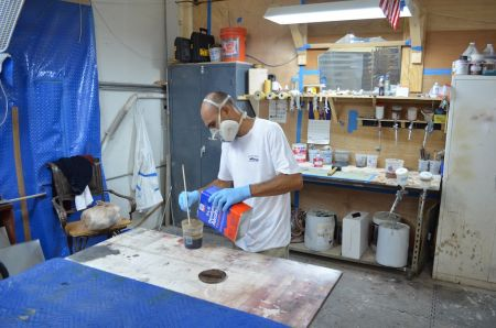 An image of an employee at Dennis Boatworks mixing wood varnish in a small can.