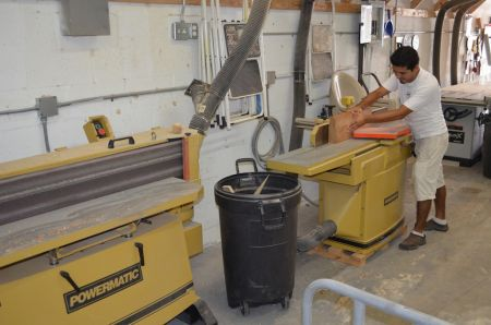 An image of an employee cutting wood for Dennis Boatworks.