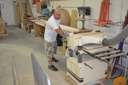An image of an employee carefully measuring wood for Dennis Boatworks.