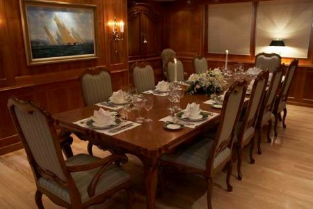 Image of wooden dining interior with 10-person table custom made by Dennis Boatworks.