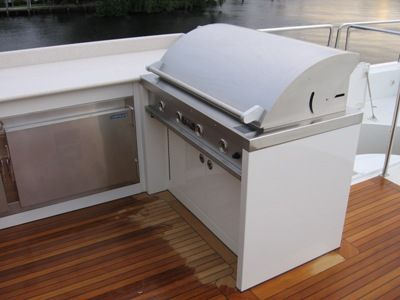 image of outdoor grill and cooler storage compartments installed on a boat with teak wood by Fort Lauderdale carpenter Dennis Boatworks