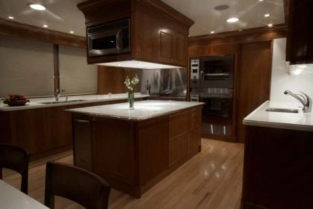 modern kitchen on a yacht white marble and dark cherry wood furniture