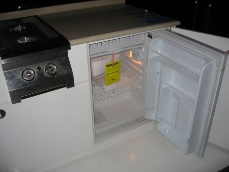 Image of a hidden mini fridge in custom cabinets by Dennis Boatworks.
