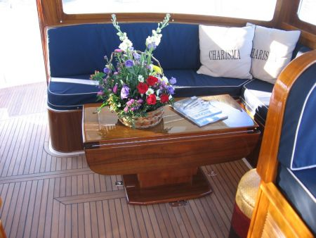 An image of a custom wooden deck table with cushioned booth made by Dennis Boatworks.