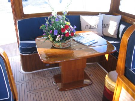 Image of expanded, hand-crafted, wooden deck table with cushioned booth created by Dennis Boatworks.