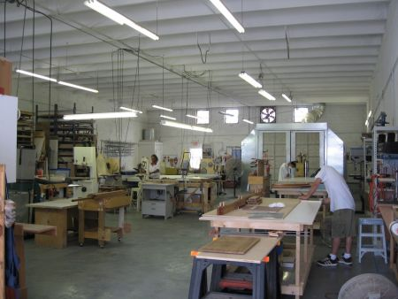 An image of the Dennis Boatworks carpentry workshop with three carpenters hard at work.