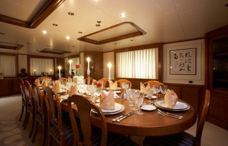 An image of an extravagant custom interior dining room with a 12-person dining table with Dennis Boatworks.