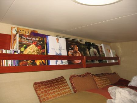 bookshelf above a bed on a yacht custom wood install by Dennis Boatworks