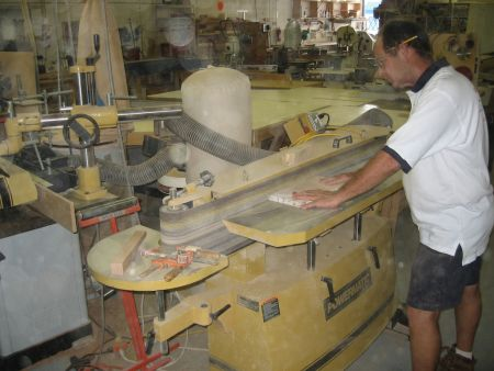 An image of an employee for Dennis Boatworks cutting wood to size.