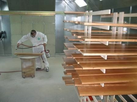 Image of a Dennis Boatworks employee staining a plank of wood.