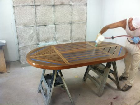 Image of a Dennis Boatworks employee finishing a hand-crafted wooden table.