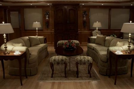 Side view of Main salon saloon living room sitting area on yacht two lamps with nightstand with third lamp lit up
