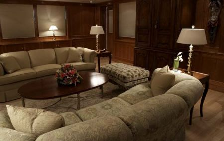 Main salon saloon living room sitting area on yacht two lamps with nightstand with third lamp lit up