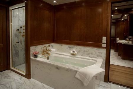 marble master bathroom tub and shower elegant high class shiny sparkling well lit yacht with towel