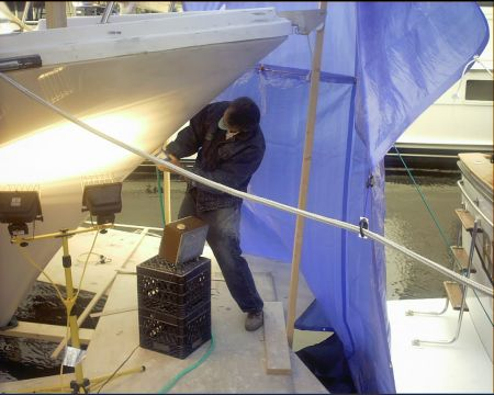 Miss-Lori-Photo of a master craftsman for Dennis Boatworks working on the bough of the ship.