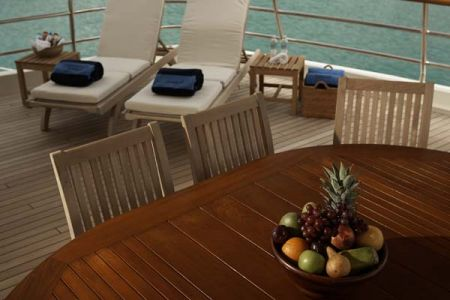 teak deck lounge chairs behind a wood table with a fruit bowl on top - 2