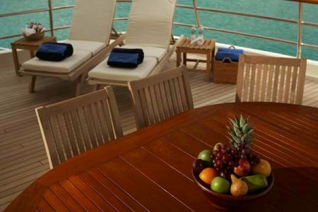 An image of the owner's deck on a yacht with custom wood flooring, two reclining chairs, and a wooden dining table created by Dennis Boatworks.