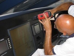 Photo of a Dennis Boatworks employee screwing a custom panel into place on the dashboard.
