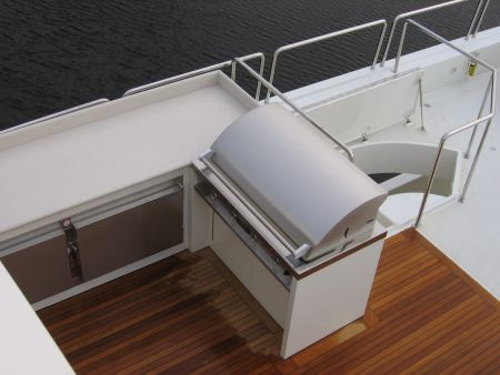 An aerial image of a custom yacht deck with wooden floors and a grill built into the countertops constructed by Dennis Boatworks.