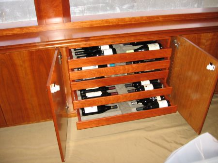 custom made wine rack on a moving ocean vessel designed and installed by the woodworkers at Dennis Boatworks