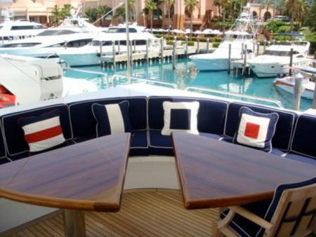 Image of wooden deck tables and a cushioned booth at the bough of the ship customized by Dennis Boatworks.