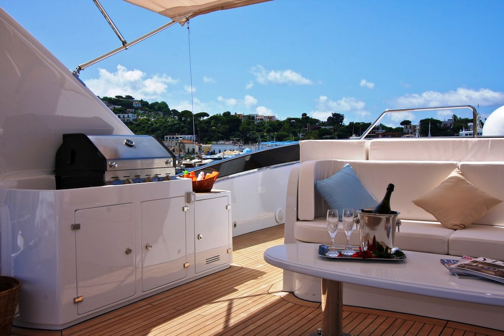 luxury yacht boat outdoor space with seating champagne glasses grill bbq and countertop open marine big sky